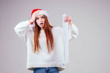 amazed and surprised redhaired ginger woman wearing red santa claus hat and knitted sweater holding long shopping receipt list in studio white background. big money xmas spending