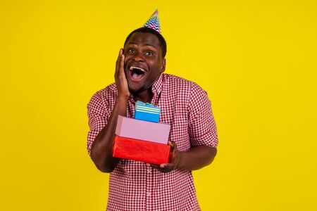 happy african american man holding boxes with birth day gifts in studio yellow background 写真素材