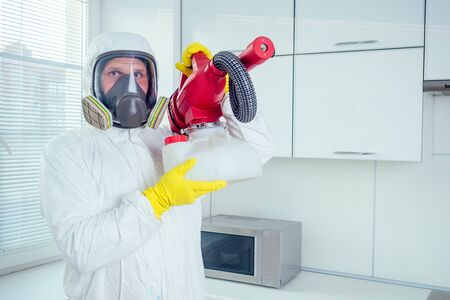 white worker spraying pesticide on induction hob Banque d'images - 133689121