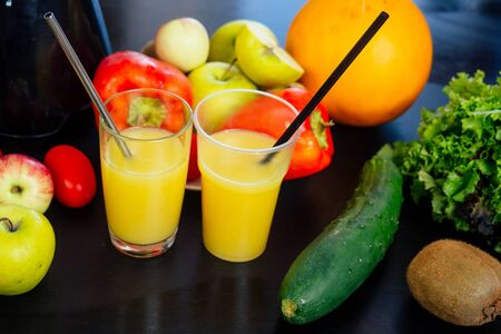 two eco steel tube with orange glasses smoothies on the wooden table with fruits and vegetables:apple,melon ,cucumber ,lettuce and kivi