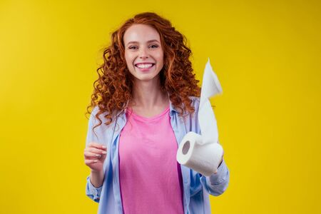 redhaired curls ginger female with hygiene eco paper on studio yellow background 스톡 콘텐츠