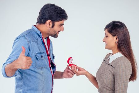 bold indian man asking her girlfriend to get wedding studio white background