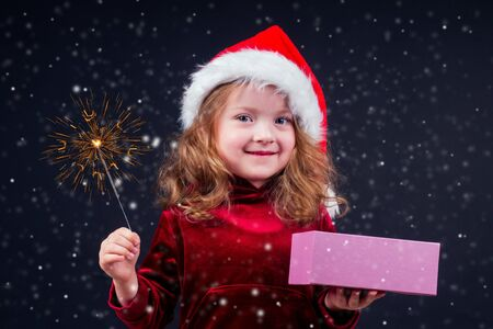little girl in warm santa hat holding bengal sparkler and white rat in studio black background snow in dark night