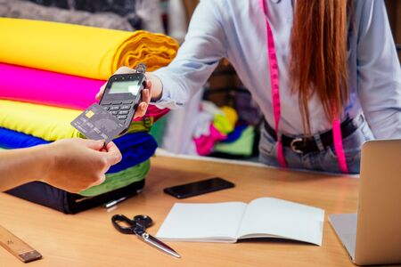Gingembre roux caissier femme dans un magasin de tissus donnant une machine de transaction de facture à une cliente