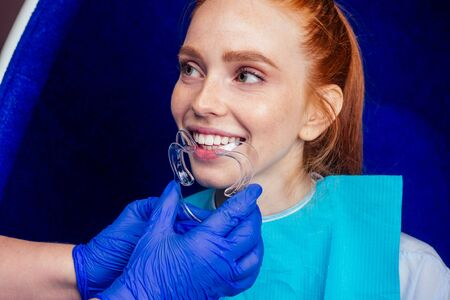 beautiful redhead ginger woman with open mouth and mouthpiece at the dentist wearing plastic whitening tray Foto de archivo