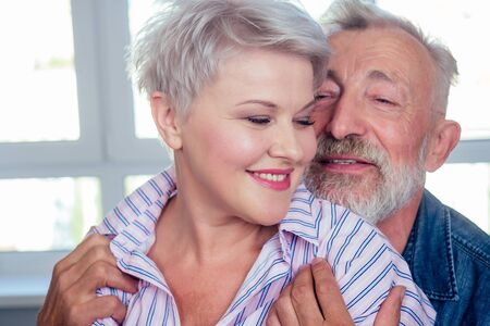 old man hard hugging her young wife with blonde hairstyle and red lipstick Foto de archivo