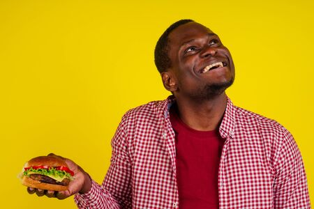 young african american man eating hamburger isolated on yellow background looking up.