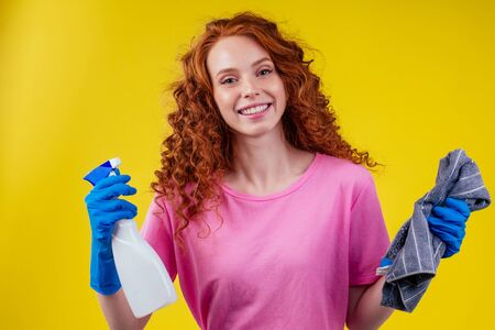 cute red haired afro curly ginger woman washing home,studuo yellow wall Zdjęcie Seryjne