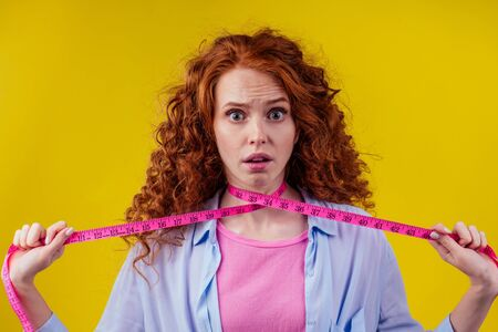 strangle redhaired ginger curly woman holding measure tape in studio yellow background.strangling her neck