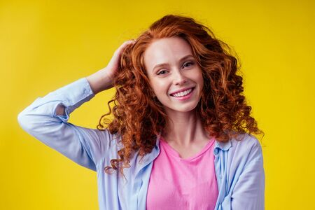 hair loss treatment prevention concept. luxury volume curly redhead ginger young woman proud her lions mane studio yellow background