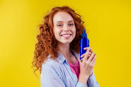 redhaired ginger curly woman holding sunscreen bottle making the right choice in studio yellow background Zdjęcie Seryjne