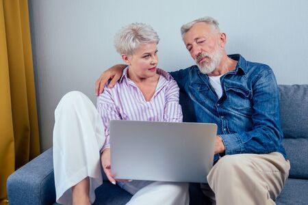 elderly couple in love sitting gray couch in living room look at screen laptop 스톡 콘텐츠