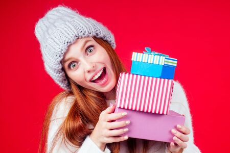redhaired ginger woman wear stylish wool hat and white sweater looking at camera and hiding behind three boxes witg gifts copyspase in studio red background