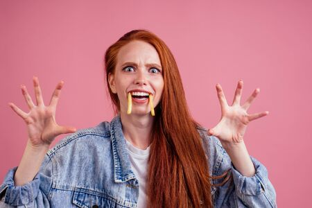funny redhaired ginger woman with potatoes like canine tooth scaring, her hands want grab you in studio pink background. fright candies or life concept Zdjęcie Seryjne
