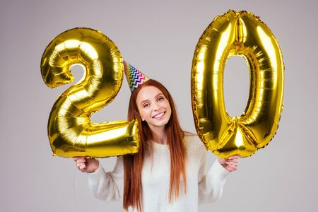surprised and amazed radhaired ginger woman with birthday cap horn holding ballons 20 years anniversary numeral in studio white background