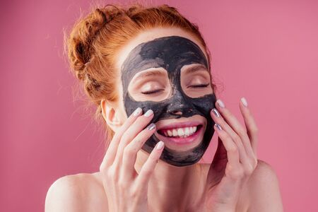 redhaired ginger teenager girl with black clay mask on her pretty face on pink studio background Zdjęcie Seryjne