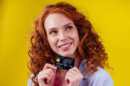 redhaired ginger woman with curly red hair having fun in studio yellow background,holding credit card and looking up