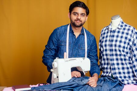 handsome indian tailor man In a stylish shirt working with dreen jeans cotton textile at home workshop yellow curtain background
