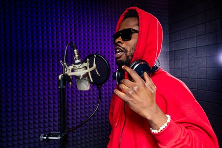 afro american man headphones in a cap and a hood sunglasses recording hip hop song track. Stok Fotoğraf