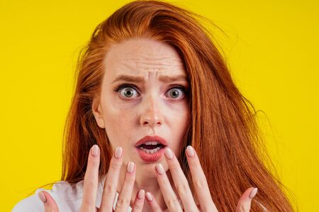 ungroomed nervous unhappy young redhaired ginger woman looking at a broken fingernail and crying .nude manicure in studio yellow background.dry and split ends of hair
