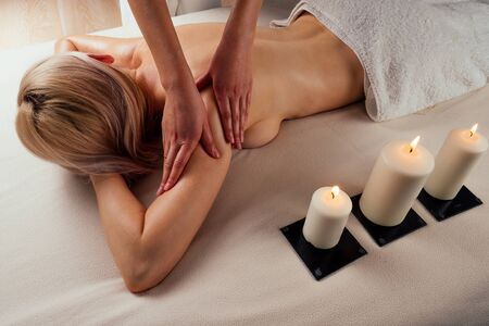 beautiful blonde female relaxation in spa salon with professional masseur shoulder body next to the candle fire 写真素材 - 132826172