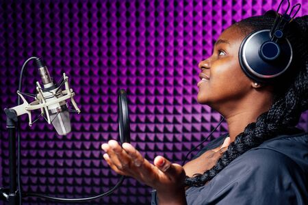 afro american woman with pigtails hairstyle headphones in a cap and a hood sunglasses recording hip hop song track.
