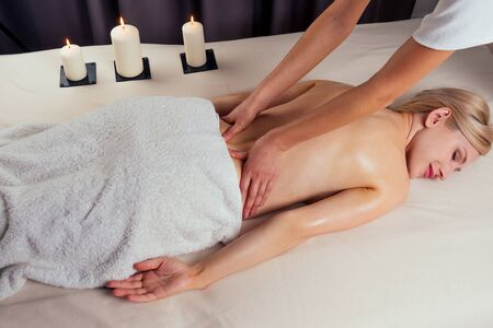 beautiful blonde female relaxation in spa salon with professional masseur shoulder body next to the candle fire 写真素材 - 132826240