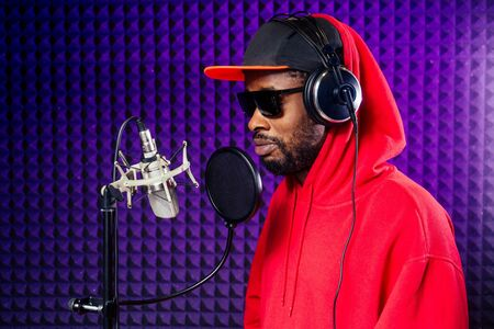 afro american man headphones in a cap and a hood sunglasses recording hip hop song track.