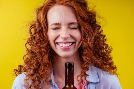 redhaired ginger woman holding non alcoholic alcohol wine bottle and feeling good emotions