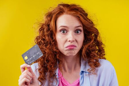Confused redhaired ginger curly woman colding plastic creditcard and looking upsad .rejection concept