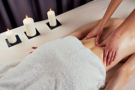 beautiful blonde female relaxation in spa salon with professional masseur shoulder body next to the candle fire