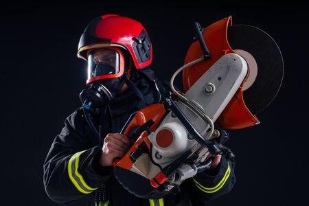 portrait strong fireman in fireproof uniform holding an ax chainsaw in his hands black background studio.