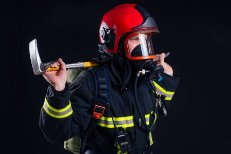 portrait strong fireman in fireproof uniform holding an ax in his hands black background studio.