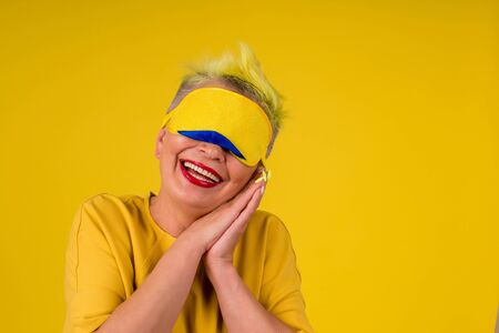 mature woman with colored stylish yellow dyed hair in warm dress with sleeping mask on her eyes background studio copy spase.