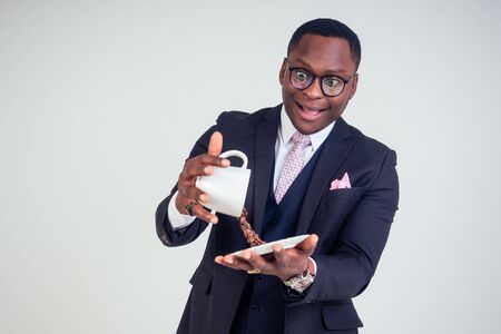surprised and amazed handsome afro american business man in a black classic suit and glasses holding a cup with flying coffee bean splash on plate in white background studio shot. Magic morning drink