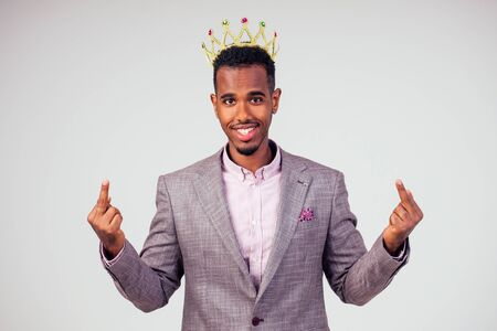 smart african american successful and rich businessman in a stylish suit and the golden crown on his head on white background in studio shot. the concept of well-deserved respect and luck