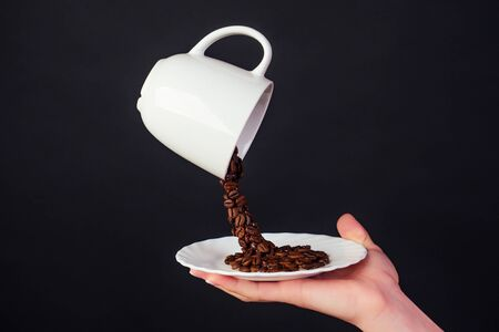 Magic coffee bean splash from a cup with plate in black background. Banco de Imagens