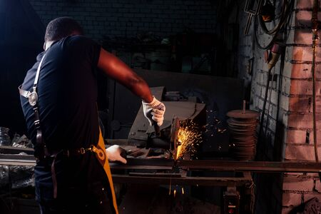 handsome african americam man forging steel next to furnace in dark workshop. small business comcept.