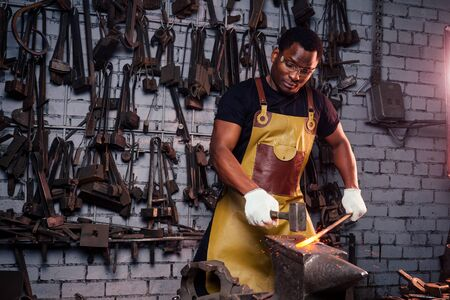hammer industry small business concept.african american man dressed in historical clothing is hammering on the anvil. A blacksmith forges a metal product Stock Photo