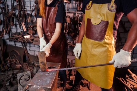 couple in love redhaired ginger young european woman and afro-american man wearing leather apron working blacksmith workshop.small family international business concept
