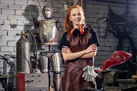 Strong and worthy pretty redhead ginher woman wearing protection helmet and leather apron with gloves holding welding machine instrument . small business concept 스톡 콘텐츠