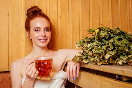 redhaired ginger woman steaming in the bathhouse with russian bunch broom drinking beers.she enjoying the sauna finnish spa