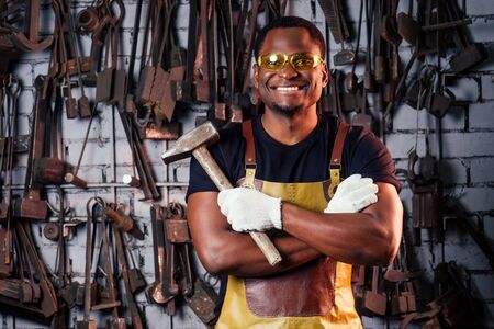 hammer industry small business concept.african american man dressed in historical clothing is hammering on the anvil. A blacksmith forges a metal product