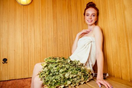 redhaired ginger woman steaming in the bathhouse with russian bunch birch broom .she enjoying heat sauna finnish spa,losing weight concept. Face pores opening