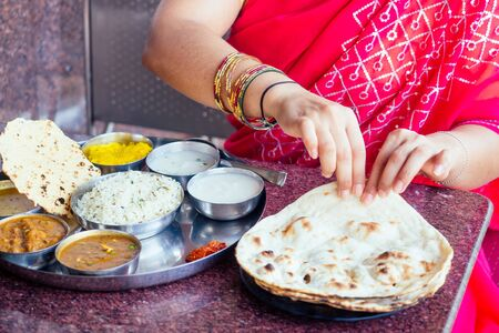 close up photo of Indian traditional vegetarian thali from rice, dal, potatoes, tomato salad on metal plate ,female hands roti india tortilla Chapati