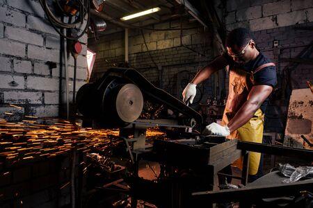 beau travailleur masculin de forgeron afro-américain travaillant en atelier, portant un tablier en cuir Banque d'images