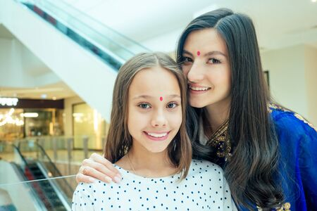Portrait of a young indian woman wearing blue sari and gold bracelet having fun with her cute daughter in shopping mall,escalator background.red religious dot on forehead