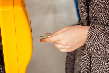 Young woman hand inserts the bus ticket into the validator, validating and ticking in Prague sity Chezh