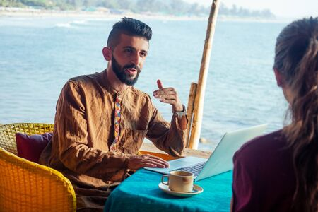 Egyptian man foreign language teacher teaching female student at tropical cafe Stock Photo