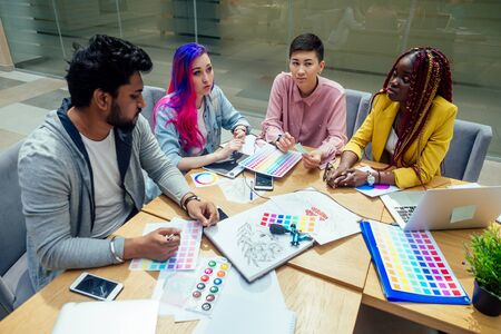 creative agency designer team working together:african american woman with dreadlocks pigtails and caucasian girl pink blue multi-colored hair communication with indian man in office